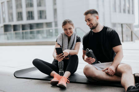 happy young couple brunette beautiful woman and handsome man in sportswear having rest on yoga mat, checking smarptones after hard street workout, healthy fit lifestyle