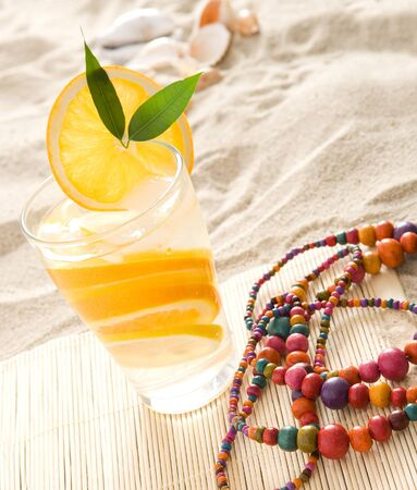 Close up on glass of lemonade on the beach  Colorful chaplet next to it   photo