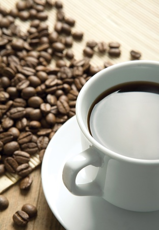 White cup of coffee on coffee beans photo