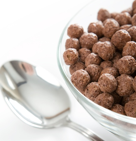 glass bowl full of chocolate balls  Steel spoon next to it  photo