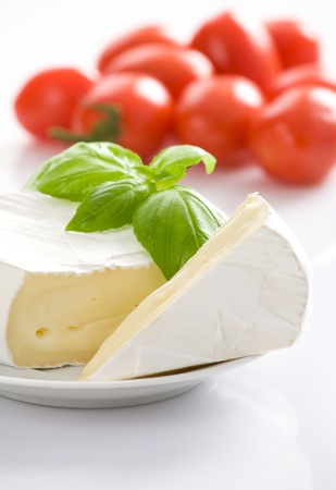 epicurean: Mouldy cheese with basil leaves on white plate   Some tomatoes in background  All on white background