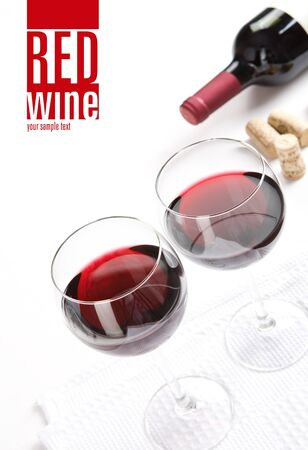 Winery menu project  Two glasses of red wine, corks   bottle of wine on white table cloth  Space for text isolated on white  Stock Photo