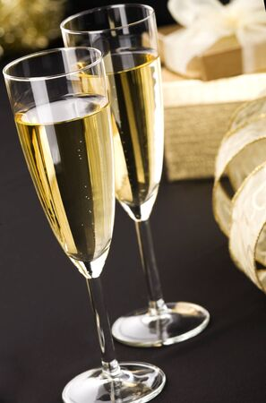 champagne flutes: Two glasses of champagne, elegant golden gift boxes with white ribbon in background  All on matt black background