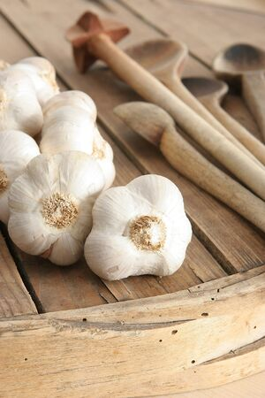 bad diet: garlic, old boards and wooden utensils in the background Stock Photo