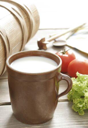 earthen pot with milk, tomatoes, salad Stock Photo
