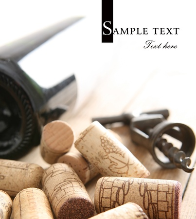 Some old wine corks  Bottle of red wine and old corkscrew in background  Space for text isolated on solid color