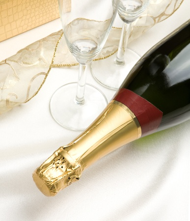 Bottle of champagne  Glasses and transparent ribbon in background Stock Photo - 13307921