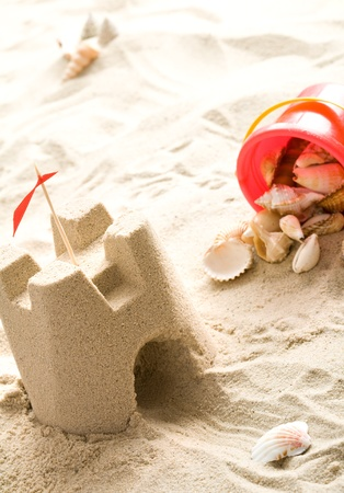 Sand castle on the beach   Red bucket filled with seashells Stock Photo