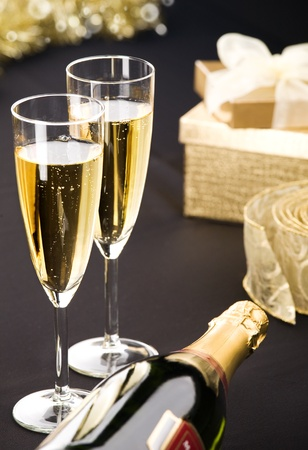 Two flutes and bottle of champagne  Golden gift box and transparent ribbon in background  All on matt black