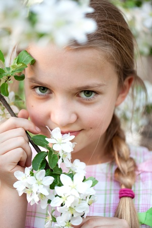 Beautiful young girl holding twig with white flowers Stock Photo