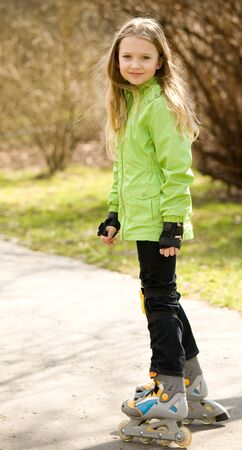 Beautiful blond young girl on rollerblades in a park photo