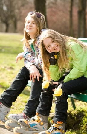 Smiling young girls on rollerblades photo