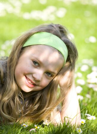 Happy little blonde girl laying on meadow Stock Photo - 13536356