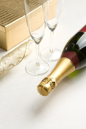 Bottle of champagne  Glasses and giftbox in background Stock Photo - 13536473