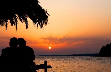 Couple on beach at Sunset Stock Photo
