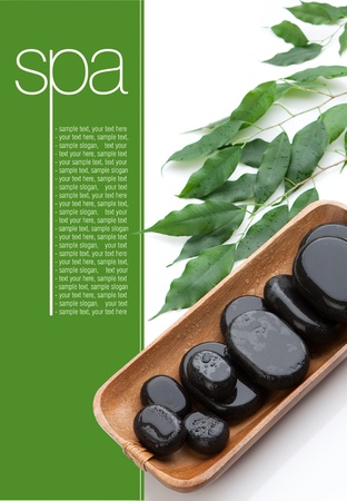 Black spa massage stones on wooden tray  Green leaves  Space for text on green
