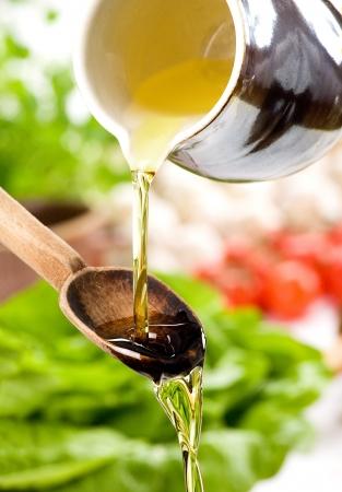 aceite de oliva: Verter el aceite en la ensalada sobre una cuchara de madera Foto de archivo