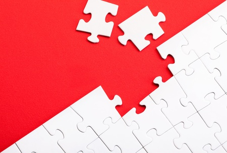 Puzzles pieces on red background photo