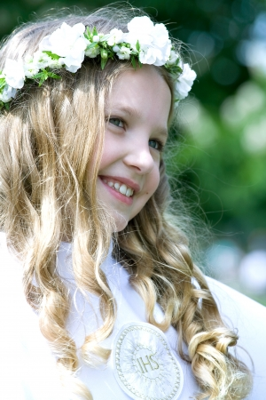 Beautiful girl in first communion uniform with ISH on chest