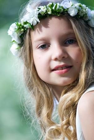 primera comunion: Hermosa chica con flor de rosario Foto de archivo