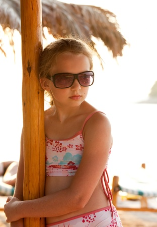 Young girl on the beach with big sunglasses photo