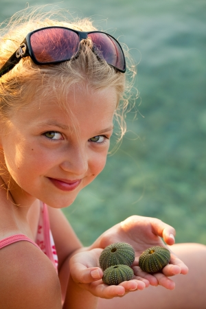 Young girl on the beach holds seashells photo