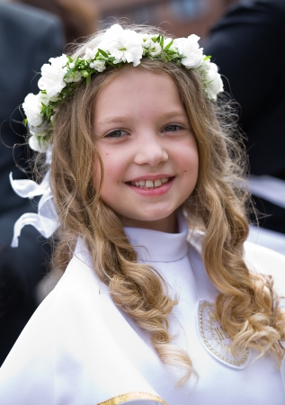 christian confirmation: First Communion beautiful girl  IHS on her chest Stock Photo