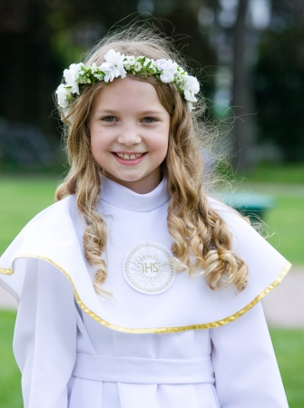 First Communion beautiful girl  IHS on her chest Stock Photo