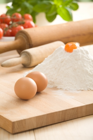 Two eggs on pastry board  Flour with yolk on top, two rolling-pins, tomatoes and basil leaves in background