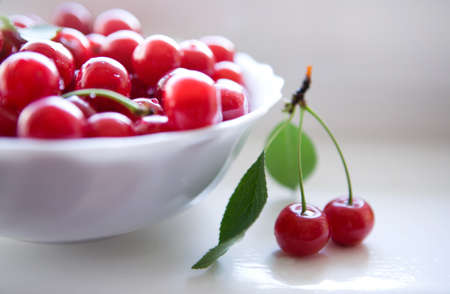 Ripe red cherries in white bowl  Little twig with two cherries and leaves photo