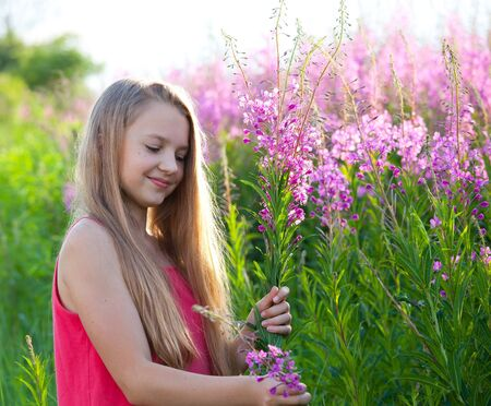Beauty young girl on meadow holds purple flowers Stock Photo - 14407545