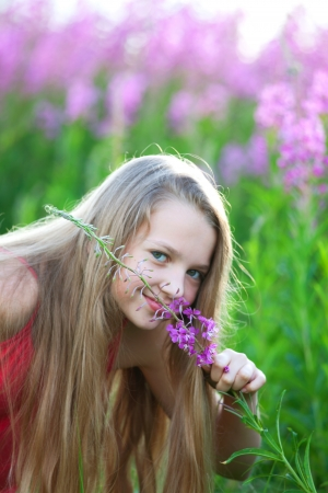Beauty young blonde girl on meadow smells purple flower Stock Photo - 14407531