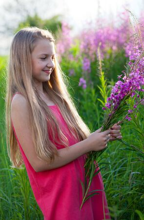 Beautiful blonde girl in pink dress holds purple flowers Stock Photo - 14407540