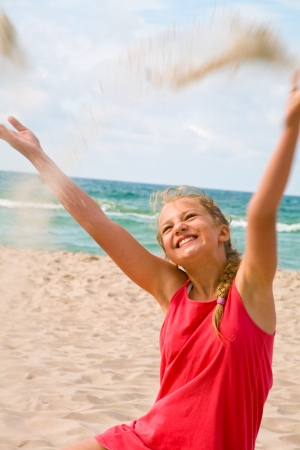 trickle down: Young blonde girl throwing sand in the air on the beach