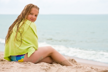 Beauty girl with blond hair and green towel sit on the beach photo