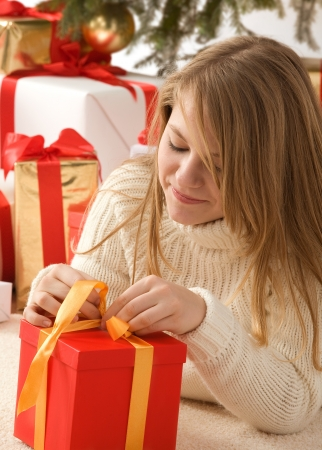 cute girl with teddy bear: Blonde girl opening her present