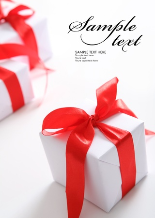 Small white gift boxes with red ribbon  Space for text photo