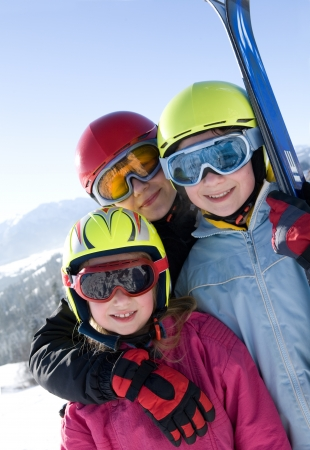 Young smiling girls wearing ski goggles  Mountains in background  Stock Photo