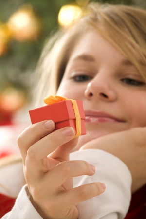 Beautiful, blonde hair, teenage girl looking at small red gift with gold ribbon. Christmas tree in background