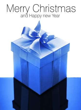 Light blue gift box with blue ribbon on white and blue reflective background   photo