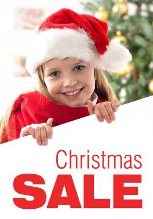 edred�n: Pelo rubio Pretty ni�a con sombrero de santa y consolador rojo bordo holding blanco con el espacio para el texto aislado en blanco �rbol de Navidad en el fondo Foto de archivo