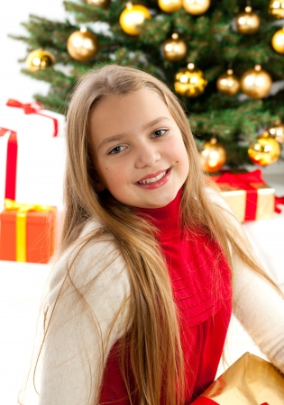 Beautiful young blonde girl in red comforter  Christmas tree with golden glass-balls in background Stock Photo - 16613846