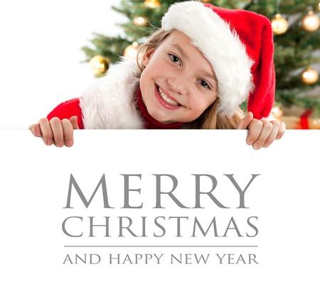 edred�n: Muchacha sonriente del pelo bastante rubio con el sombrero de santa y el rojo edred�n pizarra explotaci�n con espacio para el texto aislado en blanco �rbol de Navidad en el fondo