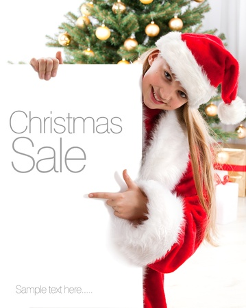 Pretty blond hair girl with santa hat holds white board with space for text Stock Photo - 16613833