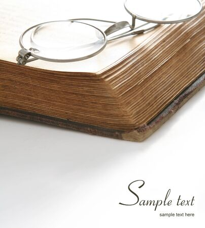 protecting spectacles: eyeglasses on old book. White background