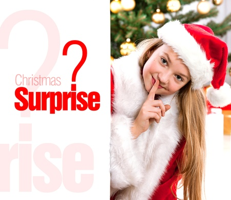 Pretty blond hair girl with santa hat and red comforter holding white board with space for text isolated on white. Christmas tree in background  photo
