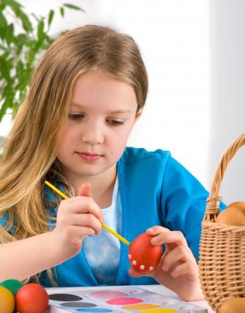 Little girl painting easter egg photo