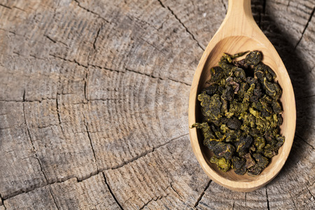 oolong: spoon with Oolong tea on wooden background