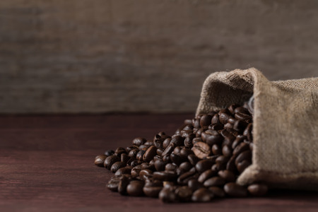 jute bag full of roasted coffee beans and scattered on a wooden table Standard-Bild
