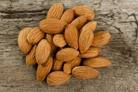tidbit: peeled almonds on wooden background. For vegetarians